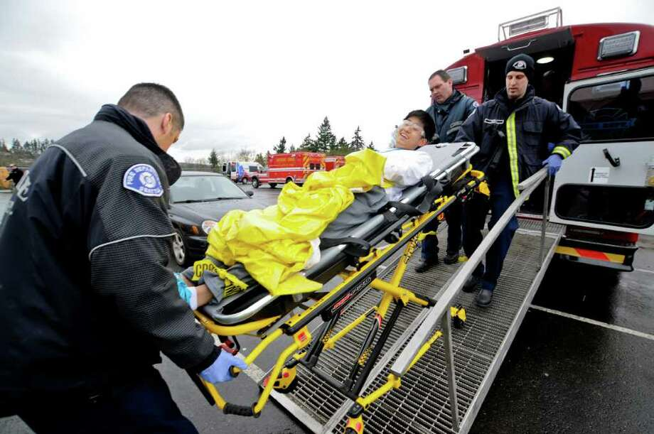 "James Bae, 15, smiles as Seattle Fire Department officers wheel him out of the ""mass casualty bus"" during a multiple shooter drill at Bellevue High School on Saturday, March 10, 2012. Planned since August, the drill tested the response and teamwork capabilities of many fire and police departments from across Western Washington. Dozens of Bellevue High School students were made up with fake wounds to make the drill more realistic, but had to wear glasses and earplugs for safety reasons. (Photo by Lindsey Wasson Photo: LINDSEY WASSON / SEATTLEPI.COM"