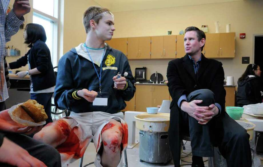 Casey Lee, 17, left, talks with Bellevue High School Vice Principal Stephen Coryelle, right, during a break before a multiple shooter drill at Bellevue High School on Saturday, March 10, 2012. Planned since August, the drill tested the response and teamwork capabilities of many fire and police departments from across Western Washington. Dozens of Bellevue High School students were made up with fake wounds to make the drill more realistic, but had to wear glasses and earplugs for safety reasons. (Photo by Lindsey Wasson Photo: LINDSEY WASSON / SEATTLEPI.COM