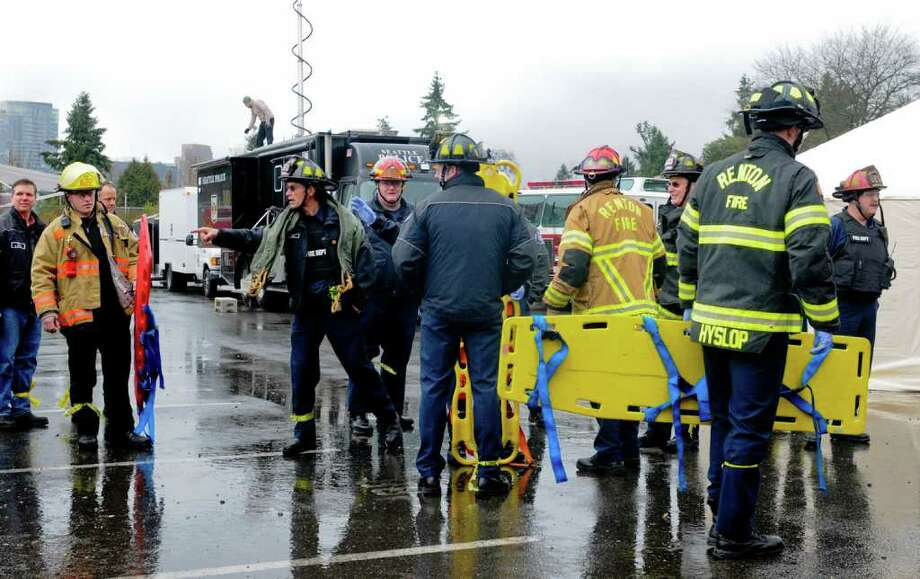Members of various local fire departments coordinate bringing in stretchers during a multiple shooter drill at Bellevue High School on Saturday, March 10, 2012. Planned since August, the drill tested the response and teamwork capabilities of many fire and police departments from across Western Washington. Dozens of Bellevue High School students were made up with fake wounds to make the drill more realistic, but had to wear glasses and earplugs for safety reasons. (Photo by Lindsey Wasson Photo: LINDSEY WASSON / SEATTLEPI.COM