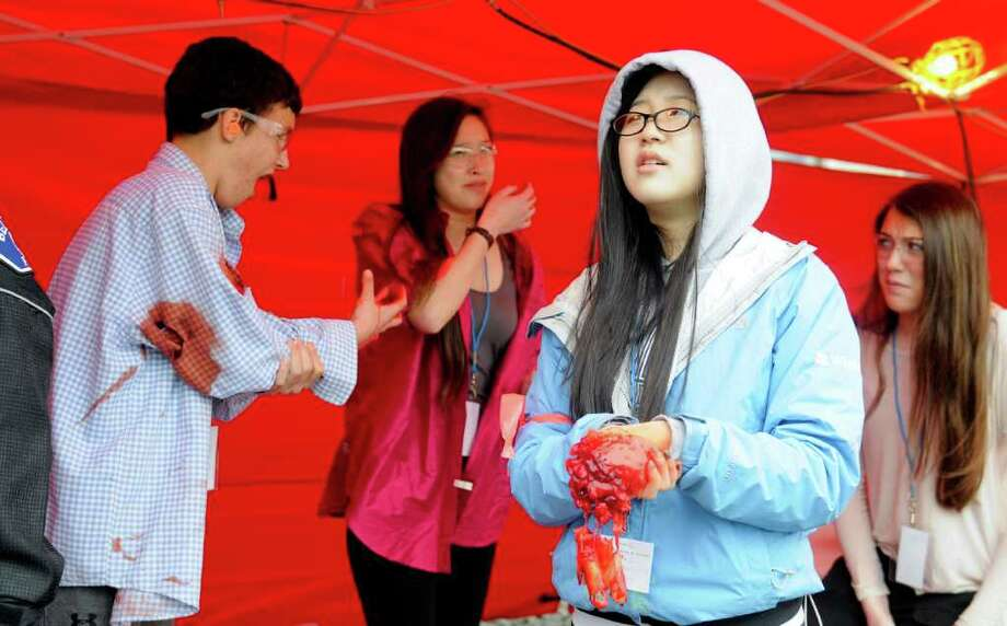 Katrina Tan, 16, hold her fake hand wound as she watches the action during a multiple shooter drill at Bellevue High School on Saturday, March 10, 2012. Planned since August, the drill tested the response and teamwork capabilities of many fire and police departments from across Western Washington. Dozens of Bellevue High School students were made up with fake wounds to make the drill more realistic, but had to wear glasses and earplugs for safety reasons. (Photo by Lindsey Wasson Photo: LINDSEY WASSON / SEATTLEPI.COM