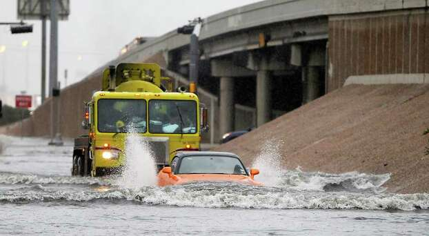 Cars make their way northbound on the flooded frontage road of I-45, between Tidwell and Parker during the downpour on Wednesday, Jan. 25, 2012, in Houston.  ( Karen Warren / Houston Chronicle ) Photo: Karen Warren / © 2012  Houston Chronicle