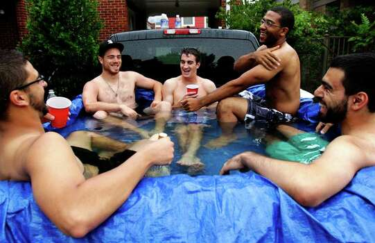 "(From left to right) Nick Lunig, Cory Swaim, Will Langevin, Mike Haynes-Pitts and Rob Granados enjoy the summer time as they sit in in the back of Lunig's truck on Pecore Street while it rained Monday, June 6, 2011, in Houston. While his original idea was to beat the heat, Lunig put a tarp in the back of his truck and filled it water. ""It's a redneck hot tub,"" Lunig said. ""Although weather conditions aren't ideal, the water is so warm and the company is so good."" Lunig said. ( Cody Duty / Houston Chronicle ) Photo: Cody Duty / © 2011 Houston Chronicle"