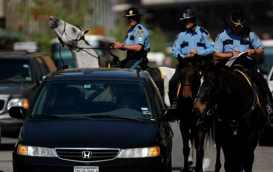 During their first day on the job, Sgt. David Cadieux (left) and his horse, Hanner, and Sr. Officer Bart Catlett, (center) and his horse, Guinness, watch Lt. Ron Wallace, head of the patrol, on his horse Jeremiah write a driver a ticket as they patrolled the streets of downtown Houston Thursday, March 24, 2011.  Lt. Wallace has 25 officers and six sergeants and 36 horses under his command.  The mounted patrol is in jeopardy of suffering from cuts or being dropped from the force all together due to budget cuts at the department. Houston police officers have been riding horses since the department began in 1941. However, the mounted patrol the department has today has been with for force for 27 years. ( Johnny Hanson / Houston Chronicle ) Photo: Johnny Hanson / Houston Chronicle