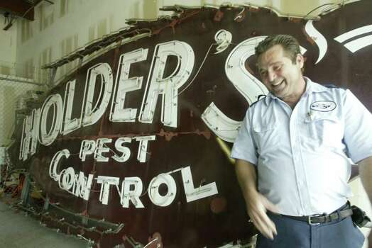 Danny Dillard has worked at Holden's Pest Control for thirty years and claims that Bubba, the giant roach sign, is the reason he applied for the job, June 25, 2004. (Meg Loucks/ Houston Chronicle).  HOUCHRON CAPTION (06/26/2004):  ROACH'S FRIEND: Danny Dillard of Holder's Pest Control shows off Bubba, the famed neon sign that now resides in a warehouse after guarding the Southwest Freeway for 42 years. Photo: Meg Loucks / Houston Chronicle