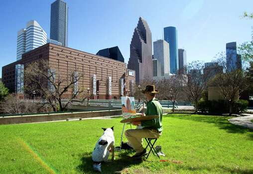 "Texas Tim Webb finishes a painting of the downtown Skyline as his dog Brandi lays in the grass in Sesquicentennial Park Sunday, March 4, 2012, in Houston. ""The temperature is perfect, and the light is clear, "" Webb said. ""I wouldn't have come down here if it were cloudy. I don't paint cloudy paintings."" Webb said that he has painted 110 paintings throughout the city of Houston since he started painting in 1985. (Cody Duty / Houston Chronicle) Photo: Cody Duty / © 2011 Houston Chronicle"