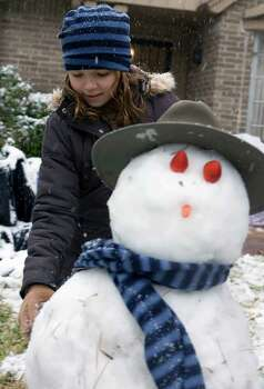 "Chloe Gentry (10yrs.) builds a snowman named ""Briskit"" with her friend Sara Wells (not shown) as snowfalls Friday, Dec. 4, 2009, in Houston. ( James Nielsen / Chronicle ) Photo: James Nielsen / Houston Chronicle"