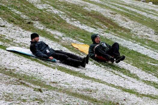 Matthew Casey , left, and Scott Trackwell, right,  both of Houston sled on snow at Spotts Park,  401 Heights Boulevard, Friday, Dec. 4, 2009, in Houston. They were using inflatable vinyl pool mattresses as sleds. ( Melissa Phillip / Chronicle ) Photo: Melissa Phillip / Houston Chronicle