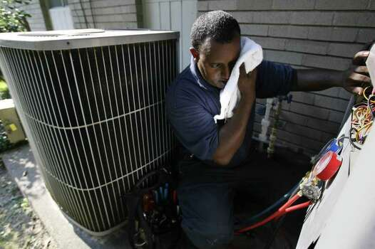 """Mo"" Rashid Kassim, a Heat, Vent, and AC Technician for Keith's AC, wipes his sweet as he checks the freon levels on an AC in west Houston during a residential call on one of the hottest days in the summer on Monday, August 13, 2007 in Houston, TX.   Photo by Mayra Beltran / Chronicle Photo: Mayra Beltran / Houston Chronicle"