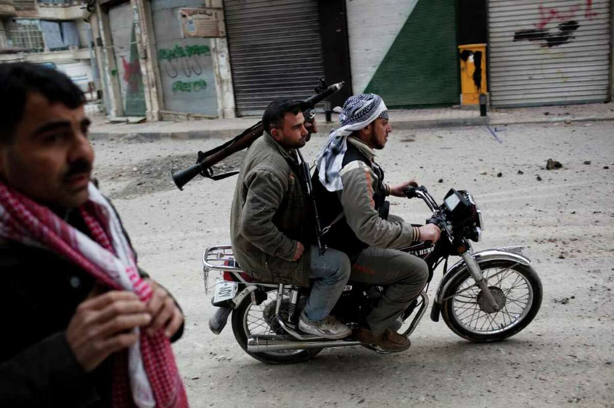 Free Syrian Army fighters ride toward Idlib, in north Syria, where tank shells recently pounded the city.