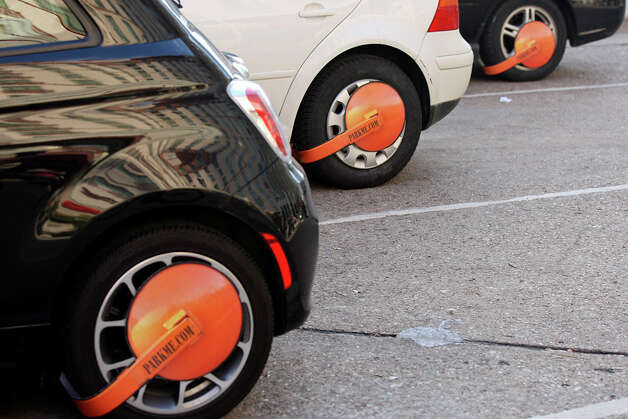 Cars with paper boots from the ParkMe app during South by Southwest  on March 11, 2012,  in Austin. Photo: EDWARD A. ORNELAS, Edward A. Ornelas/Express-News / © SAN ANTONIO EXPRESS-NEWS (NFS)