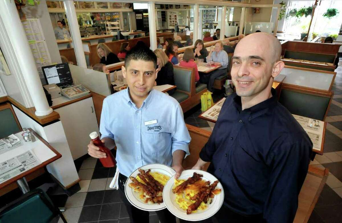 Makis Mejia holds breakfast servings next to Costas Mavridis, manager at Dimitri's Diner in Ridgefield Friday, March 9, 2012.