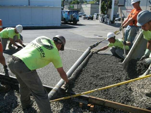 "Workers finish a section of Bellingham's new trail link, which includes ""poticrete,"" an aggregate mix containing 20 percent crushed toilets. Photo: City Of Bellingham"