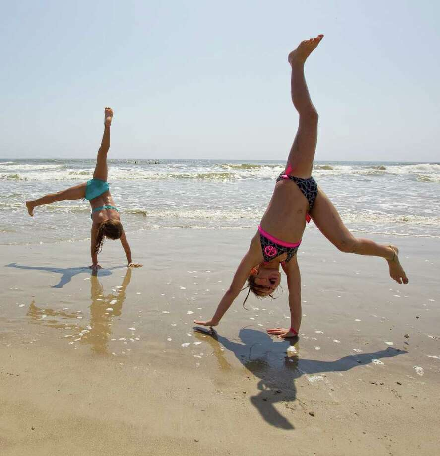 Gracee Stifflemire, 7, and her friend Harlee Taylor, 7, both of Caldwell, Texas, do cartwheels and various gymnastics moves as they play on the sand with Harlee's family Tuesday, March 13, 2012, on the beach by Seawall Boulevard in Galveston. Photo: Nick De La Torre, Houston Chronicle / © 2012  Houston Chronicle