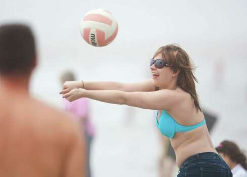 Carly Risachev, of Magnolia, plays volleyball with her father Mark Risachev, Tuesday, March 13, 2012, on the beach by Seawall Boulevard in Galveston. Photo: Nick De La Torre, Houston Chronicle / © 2012  Houston Chronicle