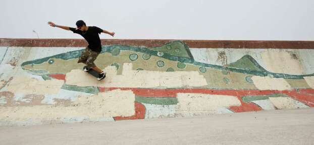 Chris Flores, 16, of Luling, Texas, tries a skateboard trick on a beach ramp, Tuesday, March 13, 2012, on the beach by Seawall Boulevard in Galveston. Flores is spending the week in Galveston with his family for Spring break and says he likes Galveston because there's lot's to do. Photo: Nick De La Torre, Houston Chronicle / © 2012  Houston Chronicle