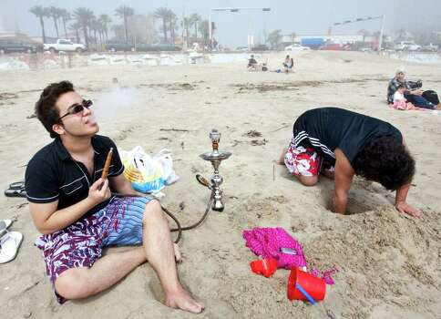 Ibraham Safa, of Dallas, left, enjoys his hookah as his friend Moe Joseph, also of Dallas, works on a sand castle, Tuesday, March 13, 2012, on the beach by Seawall Boulevard in Galveston. Photo: Nick De La Torre, Houston Chronicle / © 2012  Houston Chronicle