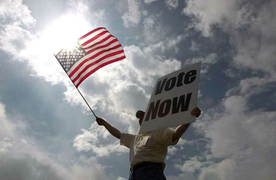 JayDanny Cooper urges Alabama residents to vote in the primary along the side of a highway March 13, 2012 in Birmingham, Alabama. As the race for delegates continues, voters in Alabama and Mississippi will cast their ballots in their primaries today. Photo: Win McNamee, Getty Images / 2012 Getty Images