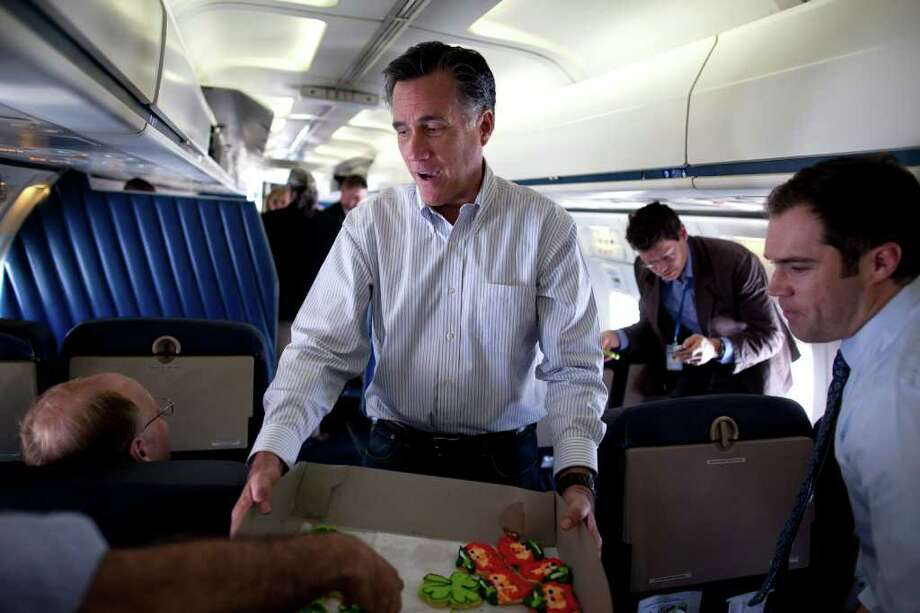 Republican presidential candidate, former Massachusetts Gov. Mitt Romney hands out cookies before departing on a flight to the next campaign stop, Tuesday, March 13, 2012, in St. Louis, Mo. Photo: Evan Vucci, Associated Press / AP