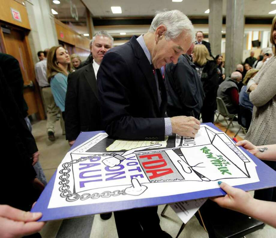Republican presidential candidate Rep. Ron Paul, R-Texas, autographs a poster at a caucus site at Shawnee Mission Northwest High School  Saturday, March 10, 2012, in Shawnee, Kan. Photo: Charlie Riedel, Associated Press / AP