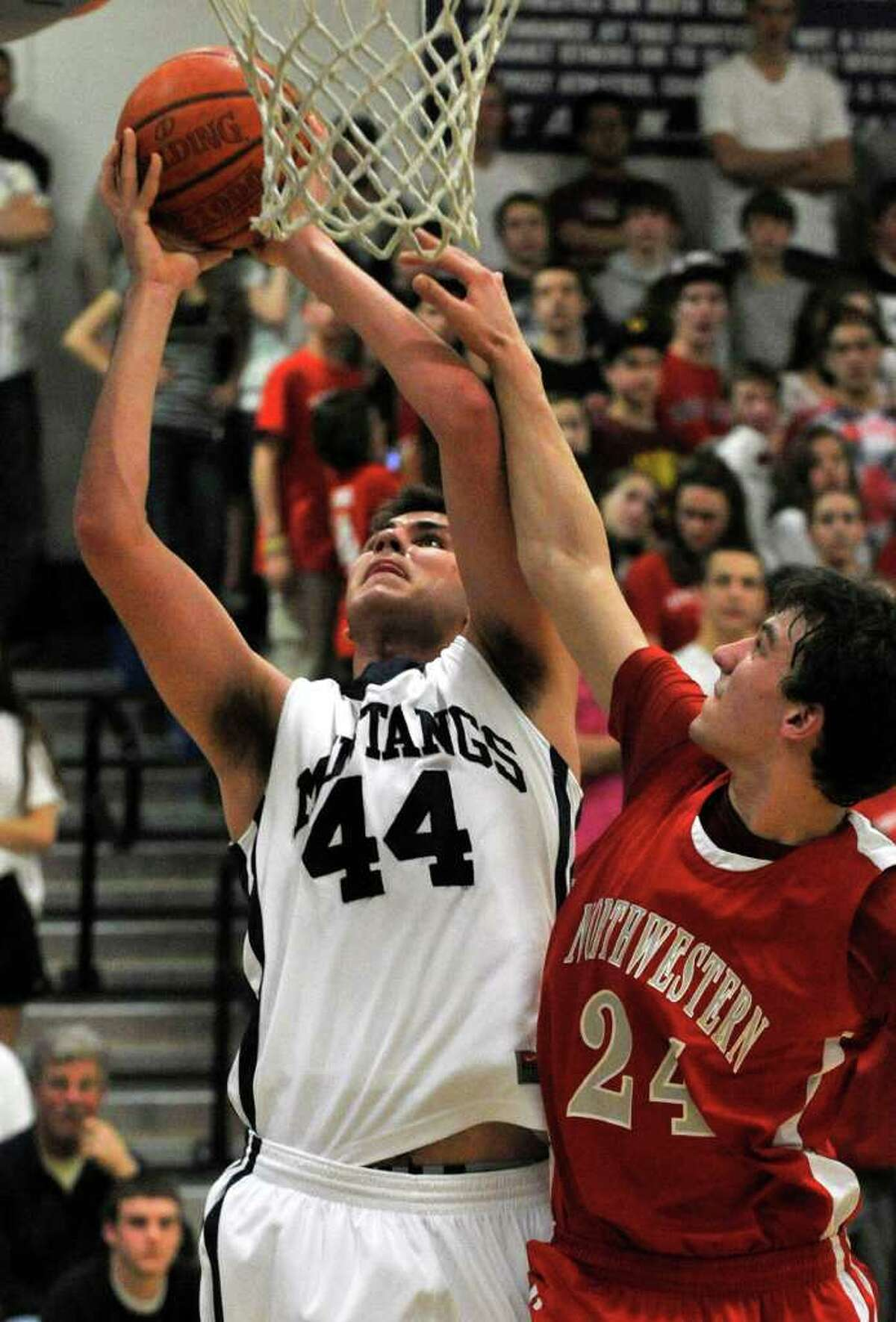 Immaculate's Vitor Melo shoots while under pressure from Northwestern Regional's Mike Jeffko during their Class S state semifinal game at Plainville High School on Tuesday, March 13, 2012. Immaculate won 76-51.