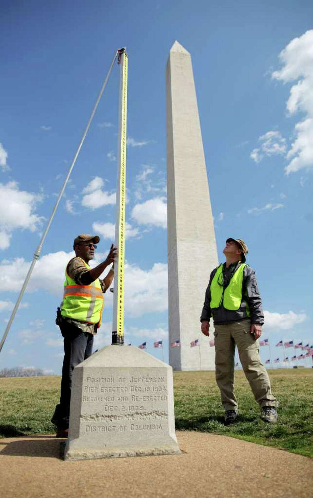 Eric Duvall, cartographic technician, left, and Jeff Olsen, geodesist, both with the National Oceanic and Atmospheric Administration (NOAA) National Geodetic Survey, measures elevation on the National Mall, with the Washington Monument in the background, Tuesday, March 13, 2012, in Washington. Government surveyors are collecting data around the Washington Monument and other sites on the National Mall that will reveal whether it has sunk or tilted since last year's earthquake. (AP Photo/Charles Dharapak)