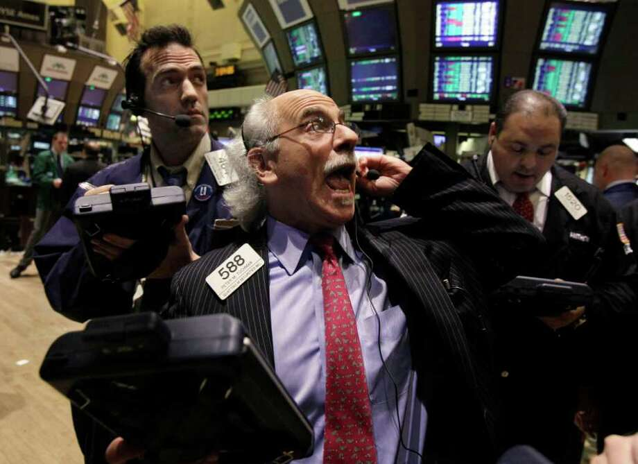Trader Peter Tuchman, center, works on the floor of the New York Stock Exchange Tuesday, March 13, 2012. The Dow Jones industrial average rose 218 points and closed at its highest level since the end of 2007. (AP Photo) Photo: Richard Drew, Associated Press / AP