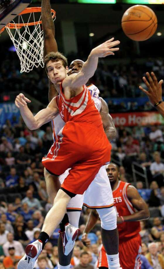 Houston Rockets guard Goran Dragic, front, of Slovenia, passes off to a teammate in front of Oklahoma City Thunder center Kendrick Perkins in the second quarter of an NBA basketball game in Oklahoma City, Tuesday, March 13, 2012. (AP Photo/Sue Ogrocki) Photo: Sue Ogrocki, Associated Press / AP