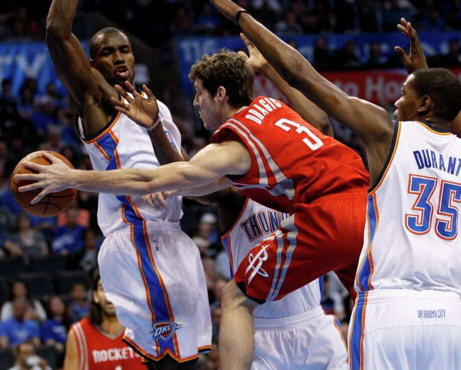 Houston Rockets guard Goran Dragic (3), of Slovenia, drives between Oklahoma City Thunder forward Serge Ibaka, left, of Republic of Congo, and forward Kevin Durant (35) in the first quarter of an NBA basketball game in Oklahoma City, Tuesday, March 13, 2012. (AP Photo/Sue Ogrocki) Photo: Sue Ogrocki, Associated Press / AP