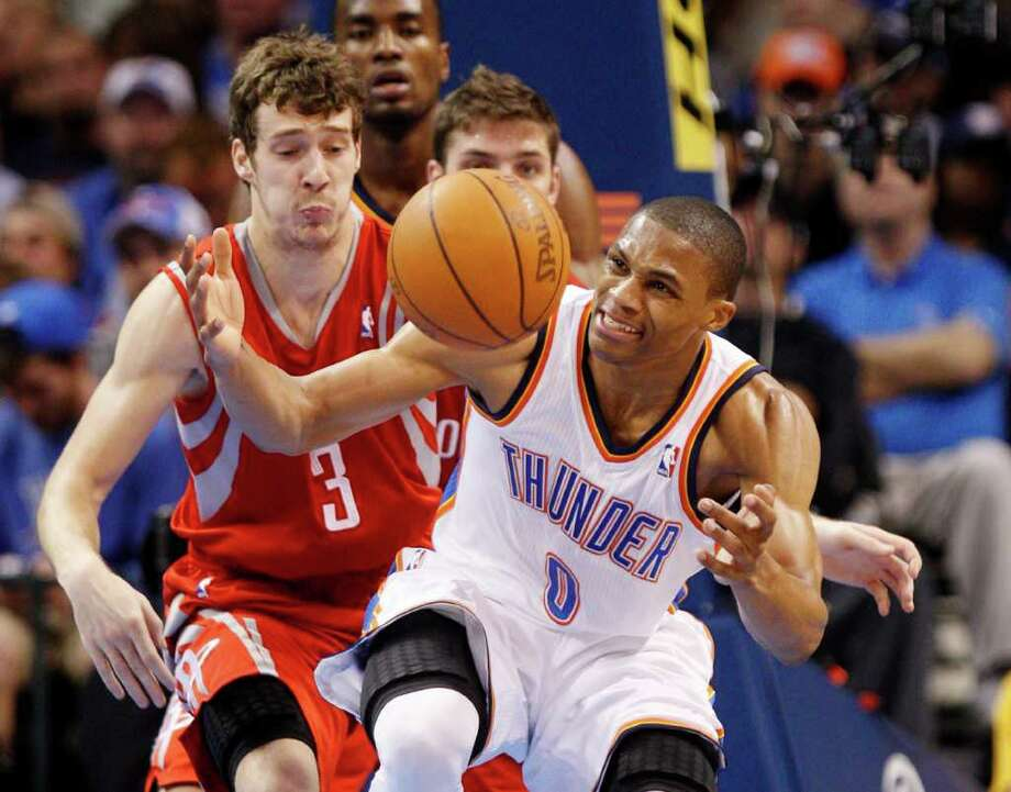 Oklahoma City Thunder guard Russell Westbrook (0) loses control of the ball as he is fouled by Houston Rockets guard Goran Dragic, left, of Slovenia, in the second quarter of an NBA basketball game in Oklahoma City, Tuesday, March 13, 2012. (AP Photo/Sue Ogrocki) Photo: Sue Ogrocki, Associated Press / AP