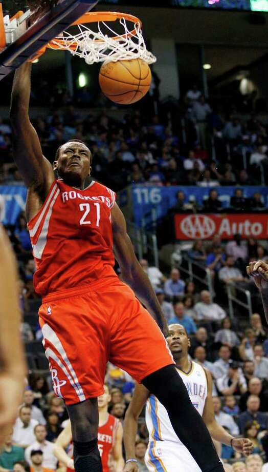 Houston Rockets center Samuel Dalembert (21) dunks in front of Oklahoma City Thunder forward Kevin Durant, right, in the second quarter of an NBA basketball game in Oklahoma City, Tuesday, March 13, 2012. (AP Photo/Sue Ogrocki) Photo: Sue Ogrocki, Associated Press / AP