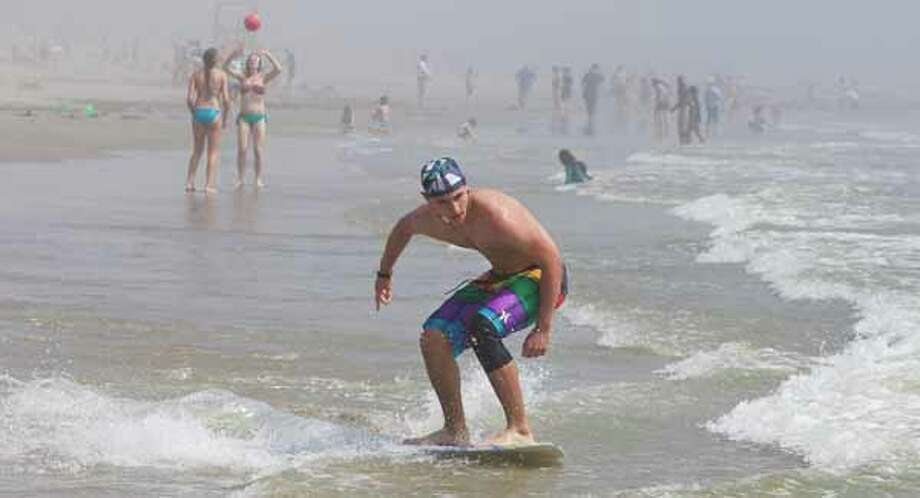 Wyatt Page, 15, of Austin, looks to hop a wave as he and his friend skim board March 13, 2012, on the beach by Seawall Boulevard in Galveston. Page says he's visiting Galveston to spend the week on the beach. Photo: Nick De La Torre, Houston Chronicle / © 2012  Houston Chronicle