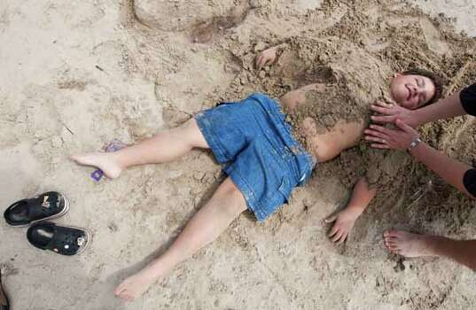 Joseph Orozco, 8, of Dallas, is buried in the sand by dad Joe Orozco as he enjoys the beach for spring break March 13, 2012, in Galveston. Photo: Nick De La Torre, Houston Chronicle / © 2012  Houston Chronicle