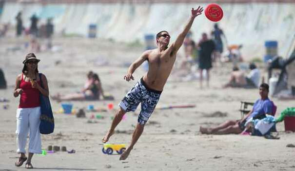 Josh Leuchtag, of Houston, reaches for a Frisbee as he enjoys some sunshine with his girlfriend, Lacey Truelove, of Houston, on March 13, 2012, on the beach by Seawall Boulevard in Galveston.  Leuchtag says he and his friends are staying in Galveston for the rest of spring break. Photo: Nick De La Torre, Houston Chronicle / © 2012  Houston Chronicle