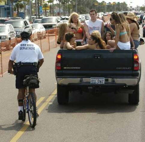 A sheriff's deputy pulls over a truck load of students riding along Padre Boulevard on March 13, 2005, in South Padre Island. (BRETT COOMER / HOUSTON CHRONICLE)