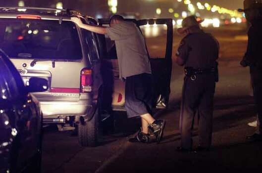 A Texas state trooper writes a ticket after pulling over an SUV with three young men traveling on Padre Boulevard early March 14, 2005, in South Padre Island. Photo: BRETT COOMER, HOUSTON CHRONICLE / HOUSTON CHRONICLE