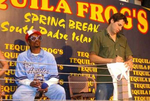 "Snoop Dog blows a kiss to the crowd while Joe Francis, founder of Girls Gone Wild video series, signs an autograph for a fan during an intermission of the ""Girls Gone Wild Spring Break Live and Uncensored"" pay-per-view event March 13, 2003, on South Padre Island. (JAMES NEDOCK / AP)"