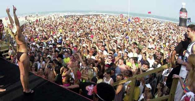 A crowd of more than 7,000 spring breakers cheer as the winner of the spring break dance contest raises her hands in victory March 14, 2002, on South Padre Island. Photo: JAMES NEDOCK, AP / THE MONITOR