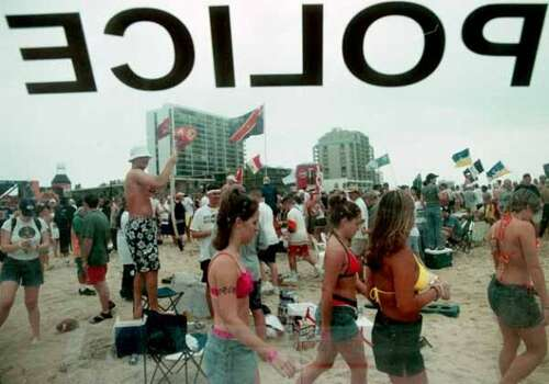 Spring breakers are seen through the window of officer Ed Pace's patrol vehicle on March 13, 2000, South Padre Island, the first day of spring break for Texas public university students. Pace watched for glass containers and leash law violations. (LESLIE MAZOCH / AP)
