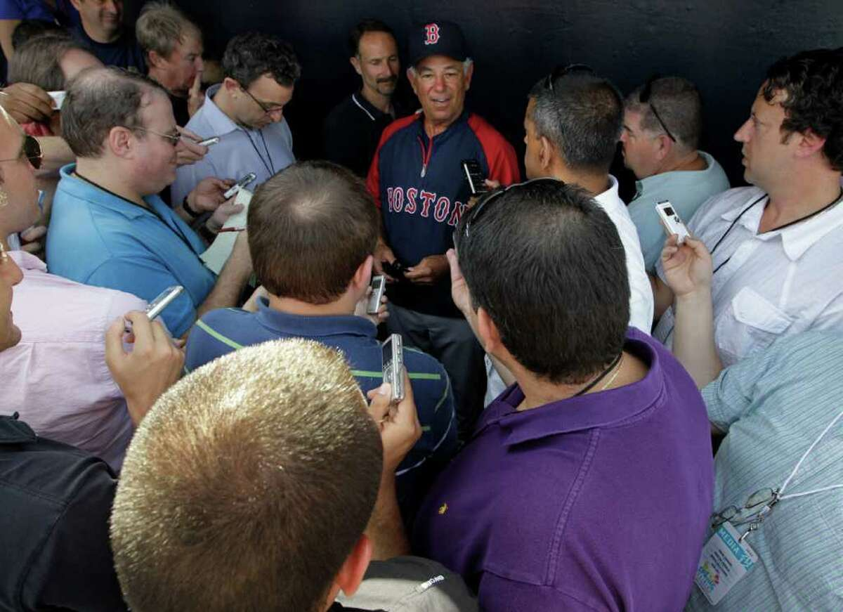 Reporters gather around Boston Red Sox manager Bobby Valentine, center, in the Red Sox dugout before their spring training baseball game against the New York Yankess at Steinbrenner Field in Tampa, Fla., Tuesday, March 13, 2012.