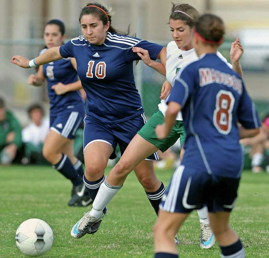 Reagan's Victoria Kustelski (center) slips a pass through against Jacqueline Ponce (10) and Chickie Murphy as Reagan plays Madison in girls soccer at Blossom Soccer Stadium on March 13, 2012 Tom Reel/ San Antonio Express-News Photo: TOM REEL, Express-News / San Antonio Express-News