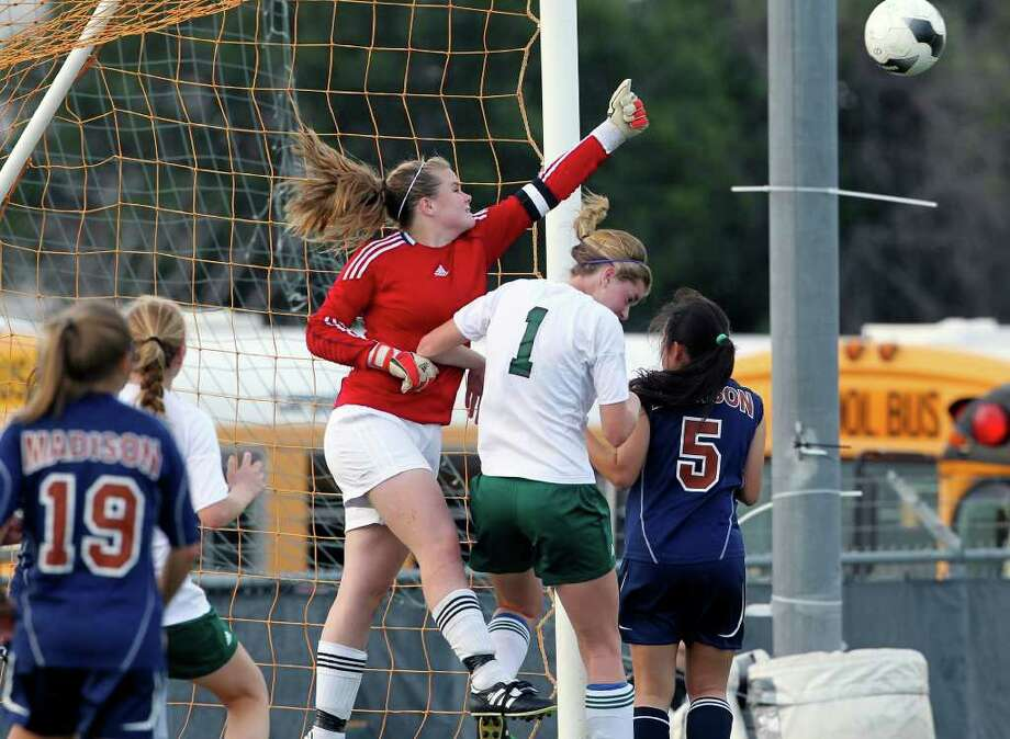 Madison goal keeper Erin Rose manages to stop one of the many shots on goal by Reagan in girls soccer at Blossom Soccer Stadium on March 13, 2012.  Reagan's  Taryn Sherman battles underneath her with Madison's Hannah Spears.  Tom Reel/ San Antonio Express-News Photo: TOM REEL, Express-News / San Antonio Express-News