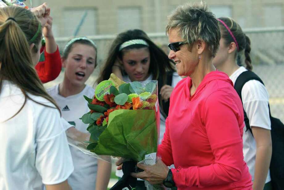 Players present flowers after coach Frankie Whitlock gets her 500th victory as the Reagan girls defeat Madison 7-0 at Blossom Soccer Stadium on March 13, 2012 Tom Reel/ San Antonio Express-News Photo: TOM REEL, Express-News / San Antonio Express-News