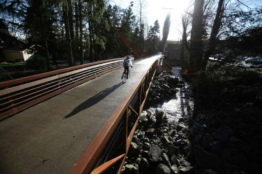 A bicycle rider crosses Lyon Creek on a new bridge, part of the newly-reopened Burke-Gilman Trail in Lake Forest Park on Tuesday, March 13, 2012. On Tuesday the popular trail was officially reopened. Photo: JOSHUA TRUJILLO / SEATTLEPI.COM