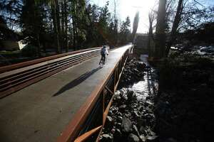 A bicycle rider crosses Lyon Creek on a new bridge, part of the newly-reopened Burke-Gilman Trail in Lake Forest Park on Tuesday, March 13, 2012. On Tuesday the popular trail was officially reopened.