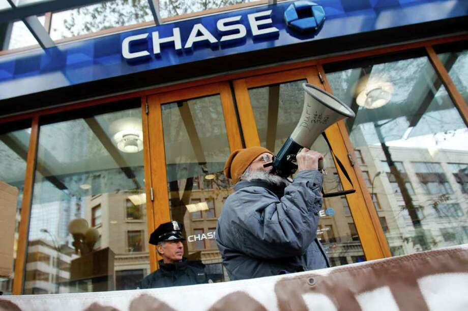 An Occupy Seattle protester demonstrates in front of a Chase bank branch on 4th Ave. in downtown Seattle on Tuesday, March 13, 2012. Demonstrators protested the bank's financial support of the Keystone XL pipeline Monday with occupations at about 12 Seattle branches. Photo: JOE DYER / SEATTLEPI.COM