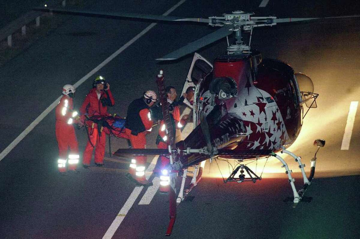 Rescue worker carry an injured person to a helicopter outside a tunnel after a bus crashed in the tunnel, in Sierre, Switzerland, early Wednesday, March 14, 2012. According to media reports more than 20 people have been killed when the bus from Belgium crashed inside the tunnel.