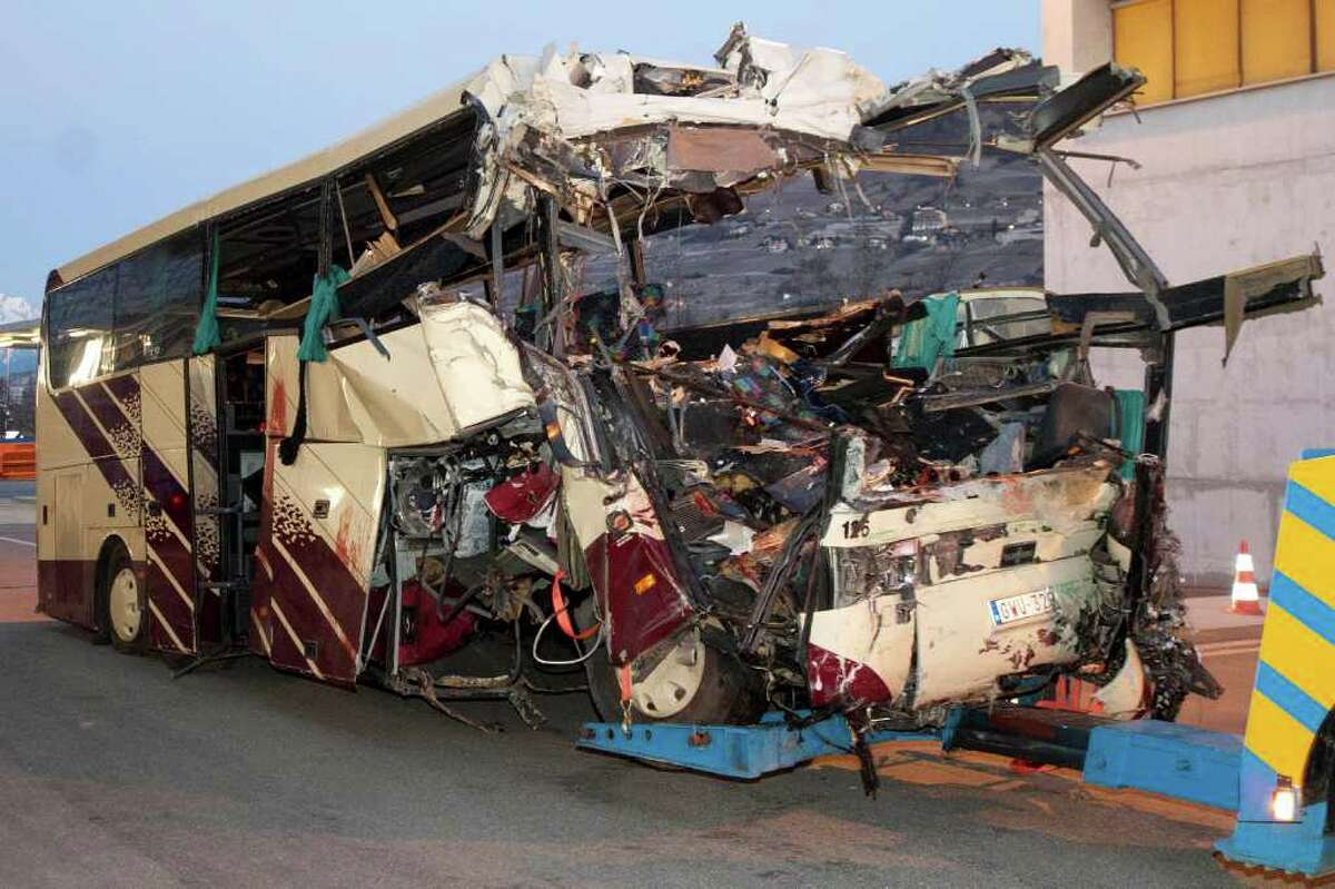 The wreckage of a tourist bus from Belgium is dragged by a tow truck outside the tunnel of the motorway A9, in Sierre, western Switzerland, early Wednesday, March 14, 2012. 28 people were killed in the bus crash.