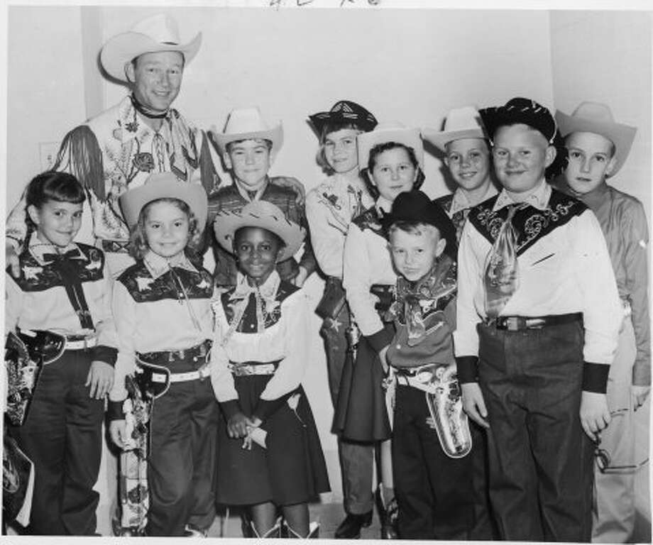 The 1957 winners of the Houston Chronicle's Roy Rogers coloring Contest pose for a photo with their cowboy hero in the outfits they won.  They not only got to meet Rogers, but they also met his wife, Dale Evans, and were guests of the famous couple at their performance at the Houston Fat Stock Show, now called the Houston Livestock Show and Rodeo.  First-place winners were, front row from left to right, Kathy Carroll, Webster; Sandra Honea, Houston; Jamie Jones, Houston; Bobby Furra, Cushing; and Ronald Krischke, Schulenburg.  Back row, from left to right, are Rogers; Nickie Davenport, Houston; Helen Childeck, Yoakum; Nancy Sherrill, Genoa; James Hale, Raywood; and Jimmy Payne, Houston. (Houston Chronicle)