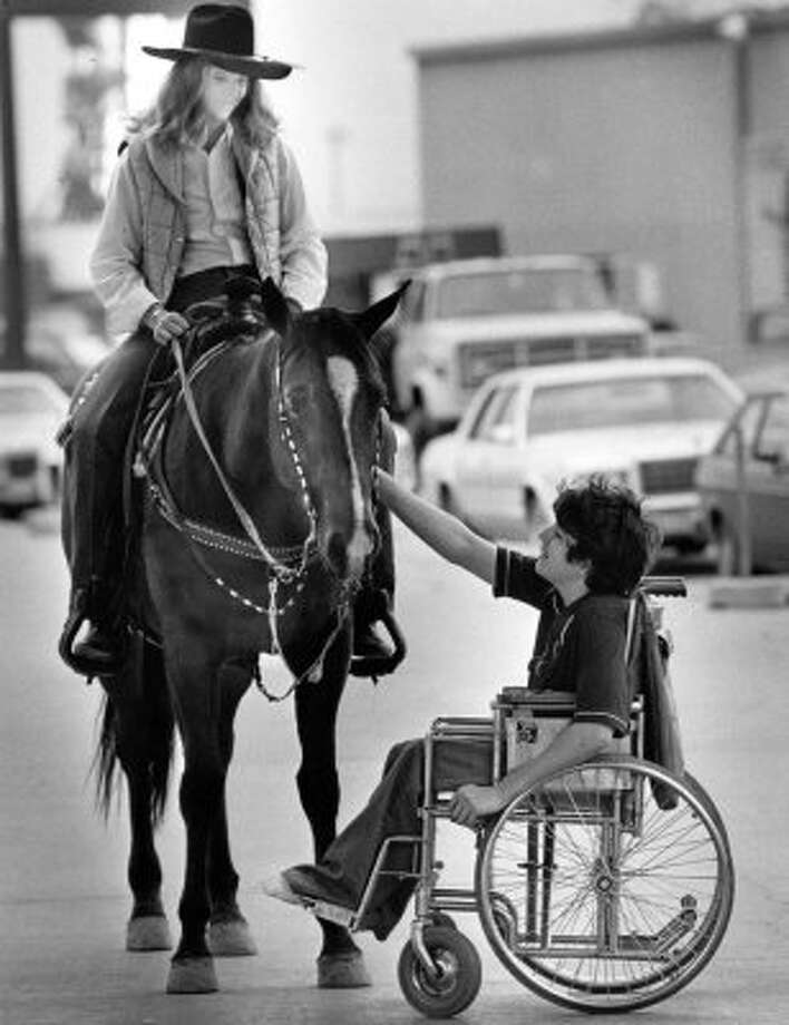 Stuart Barret, 16, of Houston reaches up to pat Laura Grawunder's horse. (03/04/1982) (STEVE UECKERT / HOUSTON CHRONICLE)