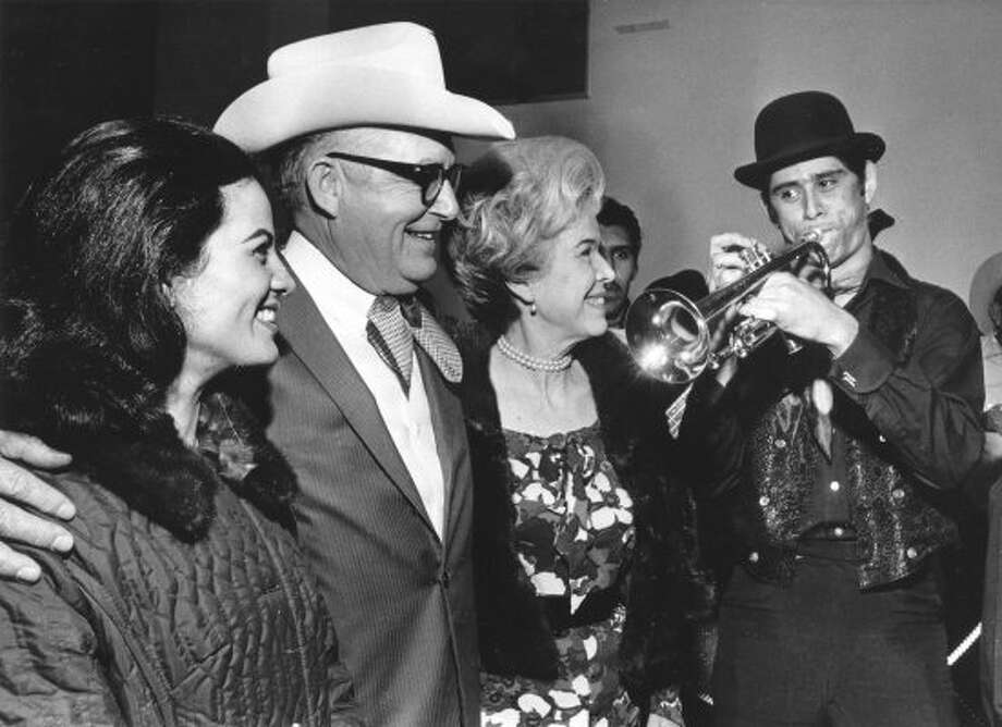 Moon Glows trumpeter Roland Martinez serenades Stock Show President Buddy Bray and two lovely ladies - Costa Rica's Lesbia Lopez (left) and Mrs. Jack Brannon.  (02/26/1970) (BLAIR PITTMAN / HOUSTON CHRONICLE)